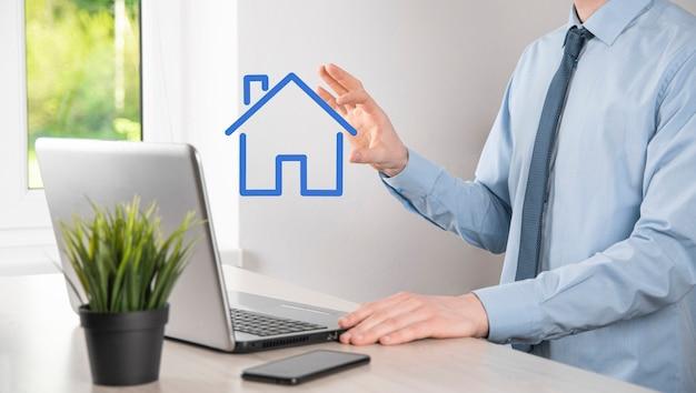 Concepto de bienes raíces, empresario sosteniendo un icono de la casa. casa en mano. seguro de propiedad y concepto de seguridad. gesto protector del hombre y símbolo de la casa.