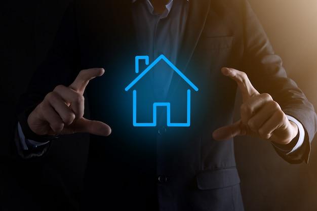 Concepto de bienes raíces, empresario sosteniendo un icono de la casa.