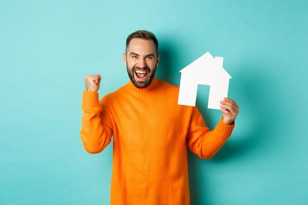 Concepto de bienes raíces. hombre emocionado diciendo que sí, mostrando el mercado de la casa de papel y mirando satisfecho
