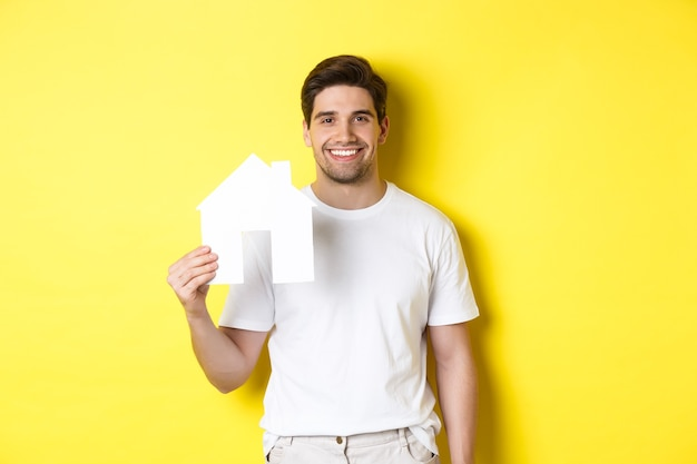 Concepto de bienes raíces. hombre joven en camiseta blanca con modelo de casa de papel y sonriendo, buscando apartamento, de pie sobre fondo amarillo.
