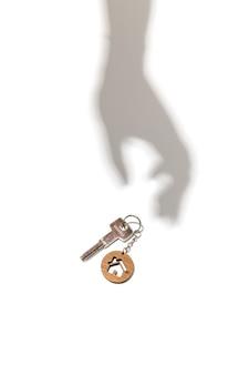 Concepto de bienes raíces llaves con llavero en forma de casa con sombra de mano sobre fondo blanco.