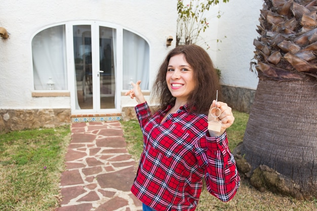 Concepto de bienes raíces y propiedad. feliz propiedad. atractiva mujer joven sosteniendo llaves mientras