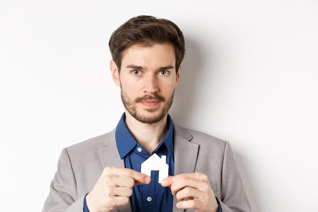 Concepto de bienes raíces y seguros. vendedor de bienes raíces mostrando un pequeño recorte de la casa de papel y mirando directamente