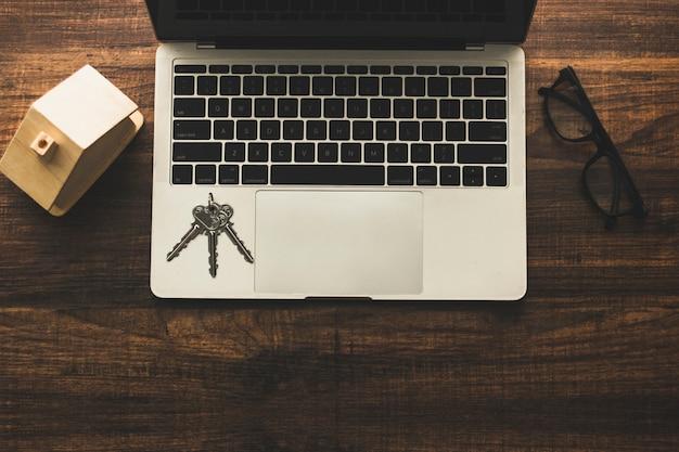 Concepto de bienes raíces, tecla de inicio y modelo de casa en mesa de madera con laptop