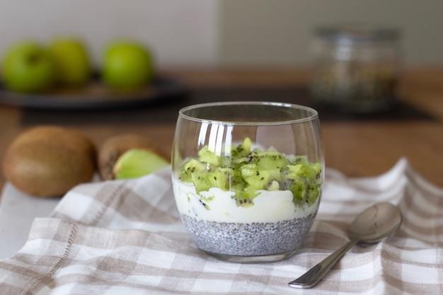 Concepto de bienestar y pérdida de peso, postre de fruta vegetariana saludable con yogur de kiwi y pudín de semillas de chía en un vaso, superalimentos de desintoxicación de verano