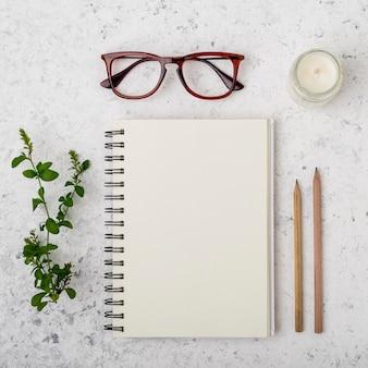 Concepto de bloc de notas con anteojos y lápices