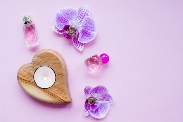 Concepto de blog de belleza. accesorios, flores, cosméticos y velas sobre fondo rosa