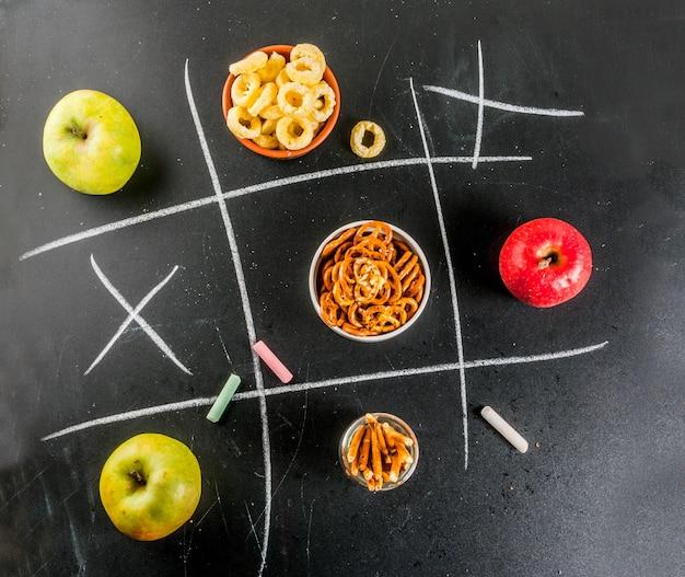 Concepto de bocadillo saludable y poco saludable de tres en raya con galletas, papas fritas y manzanas en pizarra negra