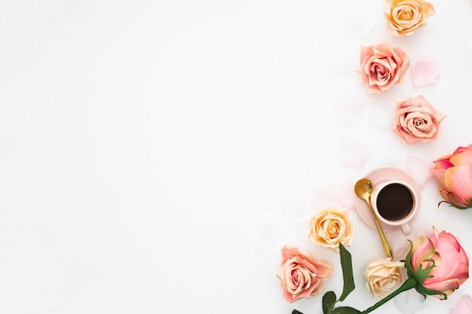 Concepto de boda hecho con rosas rosadas y una taza de café con espacio de copia