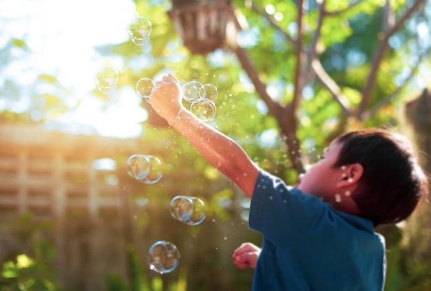 Concepto borroso niños pequeños jugando con juguetes de burbujas en el jardín