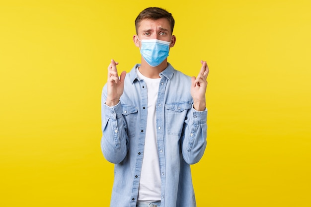 Concepto de brote pandémico de covid-19, estilo de vida durante el distanciamiento social por coronavirus. esperanzado chico blong desesperado en máscara médica, sintiendo nerviosos dedos cruzados, buena suerte, esperando noticias importantes.