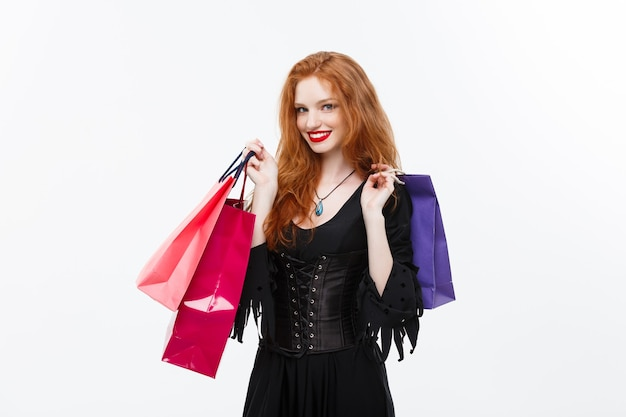 Concepto de bruja de halloween bruja de halloween feliz sonriendo y sosteniendo coloridas bolsas de compras en la pared blanca