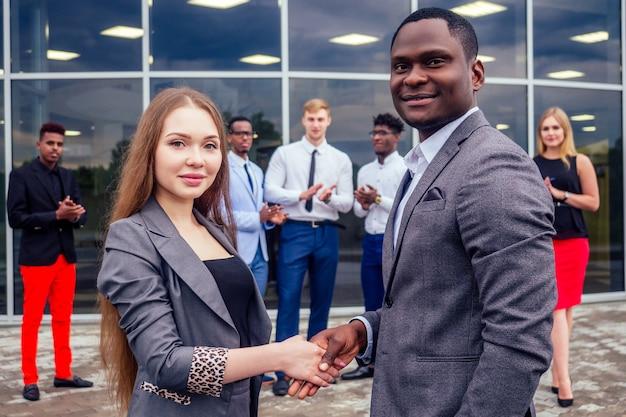 Concepto de buen trato grupo multinacional de jóvenes empresarios saludos y apretón de manos con colegas en el fondo. hermosa empresaria sonriente con socio afroamericano estrecharme la mano