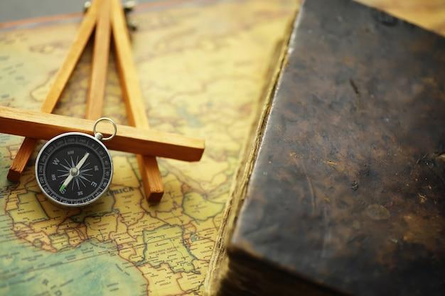 Concepto de búsqueda de viajes y aventuras. mapa envejecido vintage con un libro en mal estado y una brújula. libro en mal estado y brújula sobre la mesa.