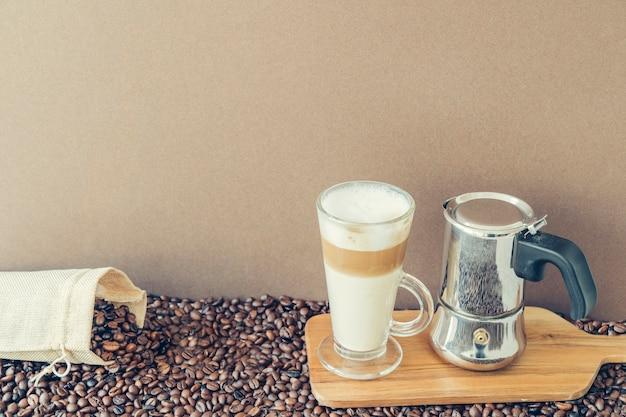 Concepto de café con macchiato a lado de cafetera