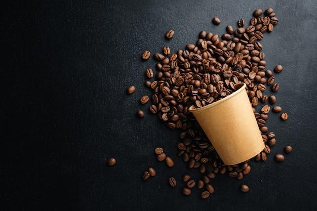 Concepto de café o desperdicio cero. granos de café en vaso de papel sobre fondo oscuro.