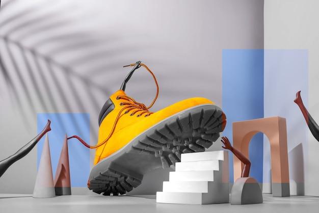 Concepto de calzado, botas amarillas en las escaleras, piernas y manos de mujer, sombra de palma sobre fondo gris, arco y otras formas geométricas, color 2021