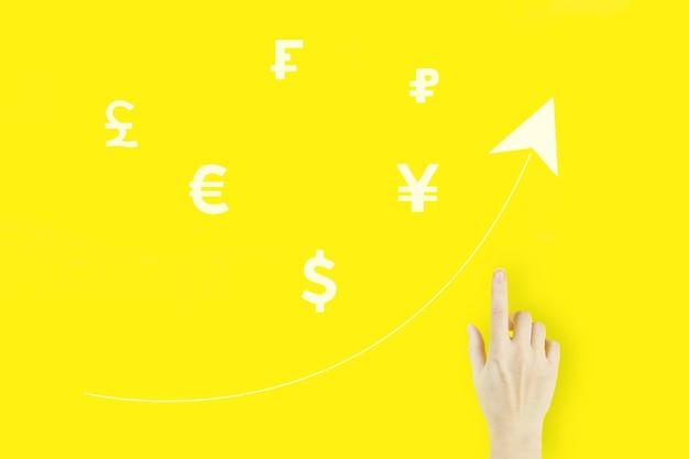 Concepto de cambio de moneda global. dedo acusador de la mano de la mujer joven con monedas del mundo del holograma y flecha hacia arriba sobre fondo amarillo. concepto de inversión financiera internacional exitosa.
