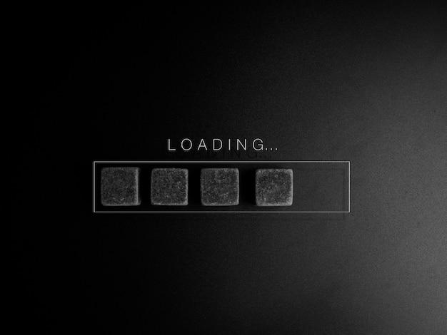 Concepto de carga. cargando ..., palabra y bloques de cubos negros en la barra de progreso sobre fondo oscuro. negocio para actuar actualizando algo a alguien o actualizado para actualizar ideas, conceptos de pensamiento creativo.