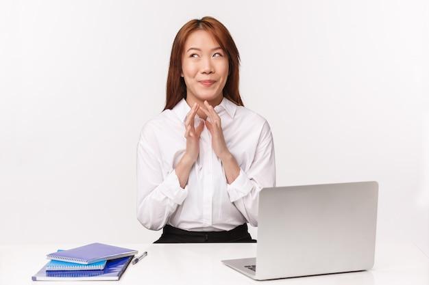 Concepto de carrera, trabajo y mujeres emprendedoras. retrato de primer plano de una mujer asiática astuta complacida sonriendo satisfecha mientras sueña con vacaciones, mucho dinero que gana en el comercio minorista, intrigante dedos de aguja