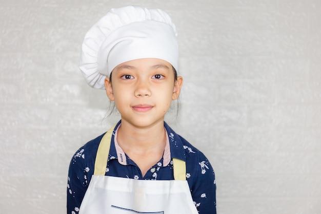 Concepto de carreras de ensueño, retrato de chef happy kid mirando a cámara con fondo borroso
