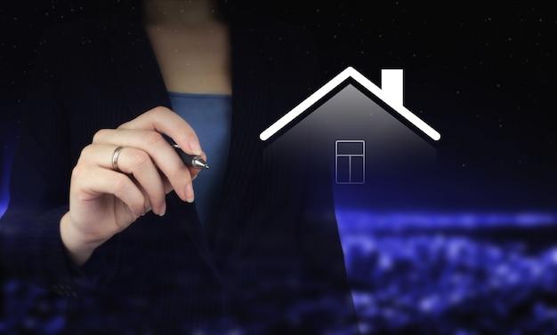 Concepto de casa inteligente, tecnología de sistema domótico. mano que sostiene el bolígrafo gráfico digital y el dibujo de holograma digital smart home firman en la parte posterior oscura de la ciudad borrosa. nuevo concepto de construcción.