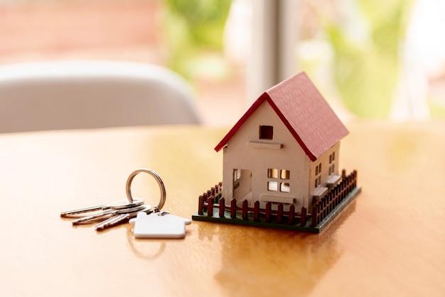 Concepto de casa modelo de juguete con llaves y fondo borroso