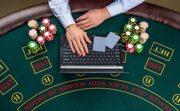 Concepto de casino, juegos de azar en línea, tecnología y personas - cerca del jugador de póquer con naipes, computadora portátil y fichas en la mesa de casino verde