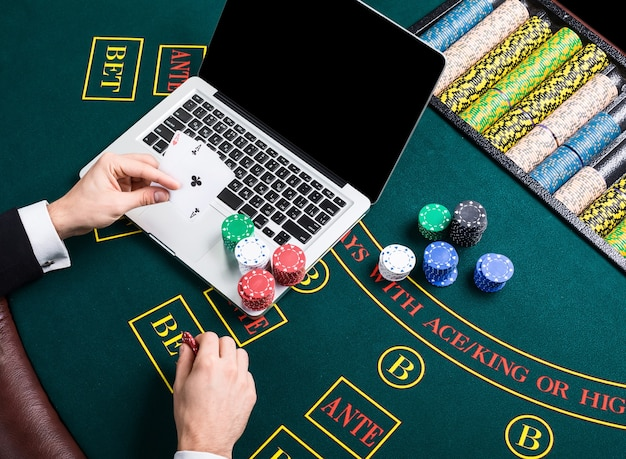 Concepto de casino, juegos de azar en línea, tecnología y personas - cerca del jugador de póquer con naipes