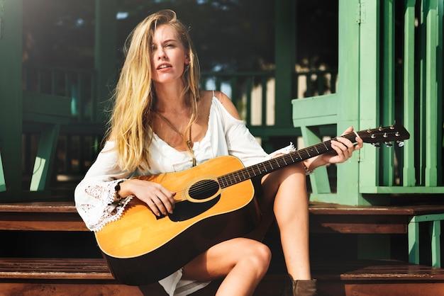 Concepto casual del ocio del instrumento de la relajación de la muchacha de la guitarra