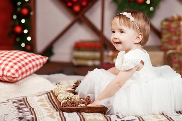 Concepto de celebración de año nuevo y navidad. niña bonita en vestido blanco jugando y siendo feliz con el árbol de navidad y las luces. vacaciones de invierno.