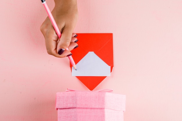 Concepto de celebración con caja de regalo en mesa rosa plana lay. mujer firma tarjeta de felicitación.