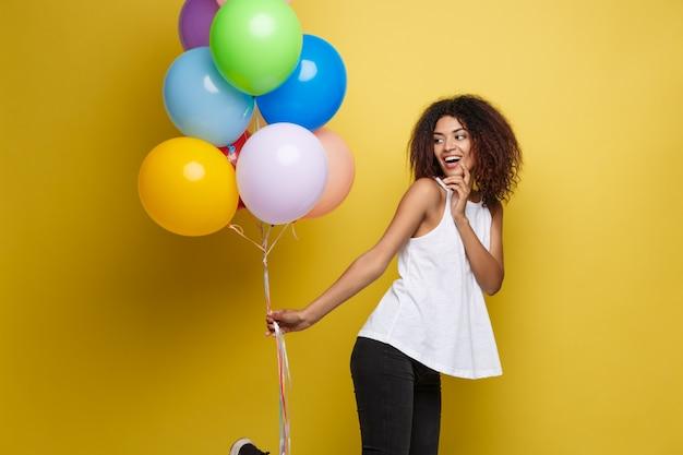 Concepto celebración - close up retrato feliz joven hermosa mujer africana en camiseta negra sonriendo con globo colorido del partido. fondo pastel amarillo del estudio.