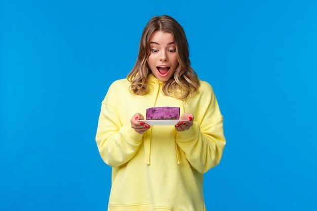Concepto de celebración, fiesta y estilo de vida. feliz y complacida chica caucásica rubia con capucha amarilla, mirando fascinado el sabroso pastel de bayas con ganas, quiere comer algo, pararse