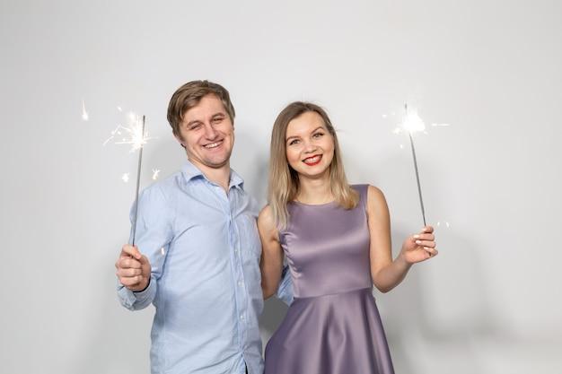 Concepto de celebración, fiesta y vacaciones - feliz hombre y mujer abrazándose sobre fondo gris con luces de bengala.