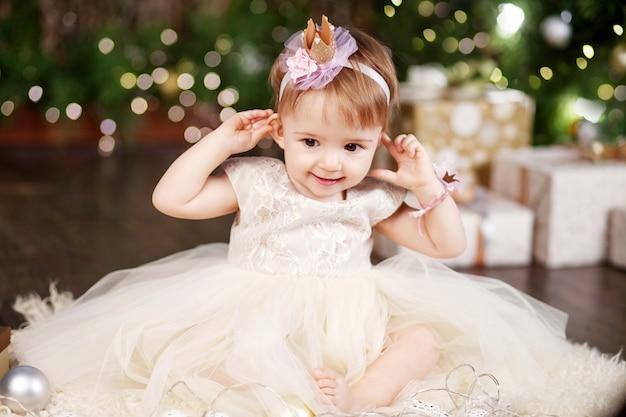 Concepto de celebración de navidad y año nuevo. niña bonita en vestido blanco jugando y siendo feliz con el árbol de navidad y las luces. vacaciones de invierno.