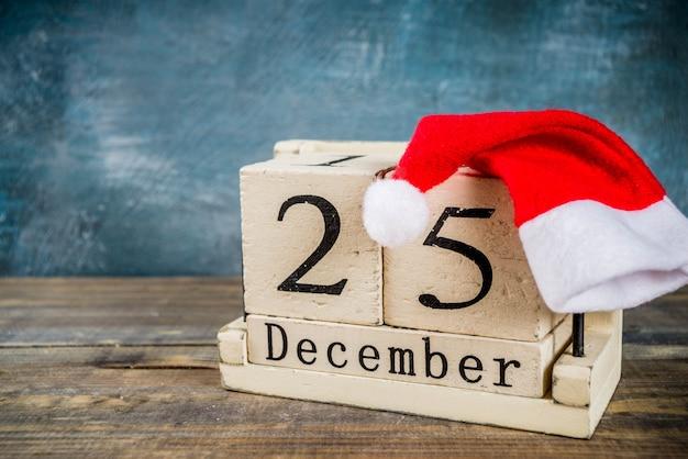 Concepto de celebración de navidad, antiguo calendario de madera de estilo retro con sombrero rojo de santa