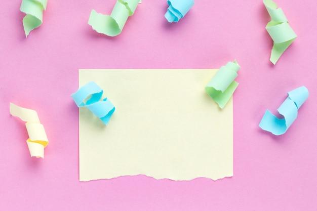 Concepto de celebración. serpentinas de fiesta de colores y un trozo de papel de nota de color roto. copia espacio