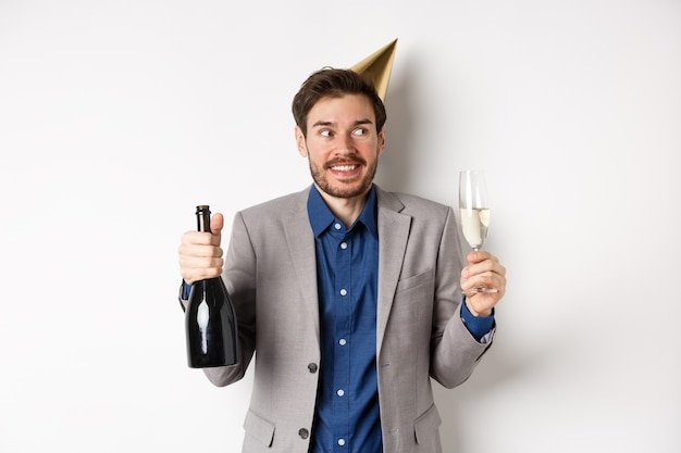Concepto de celebración y vacaciones. chico feliz cumpleaños en traje y gorro de fiesta bebiendo champán, sosteniendo una botella y vaso, sonriendo y mirando a un lado.