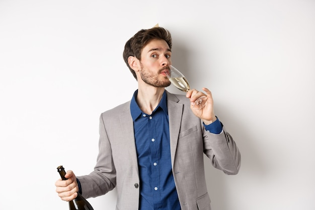 Concepto de celebración y vacaciones. hombre guapo con barba en traje y sombrero de cumpleaños con botella, copa de champán, de pie sobre fondo blanco.