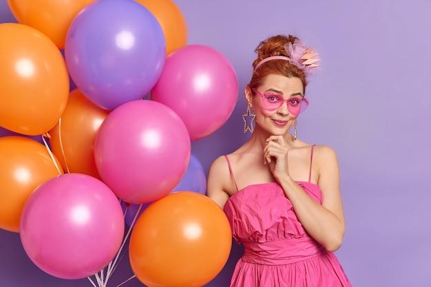 Concepto de celebración y vacaciones de personas. mujer de moda de los noventa mira con alegría a la cámara viste ropa de estilo vintage se prepara para poses de fiesta con globos