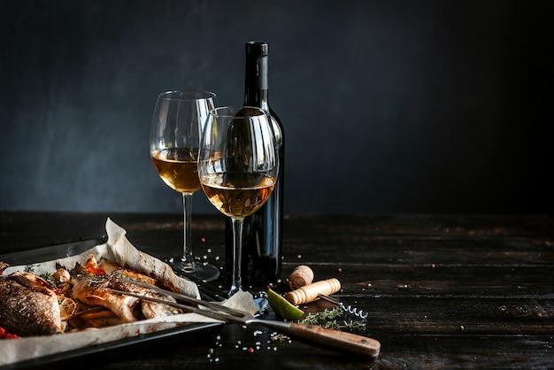 Concepto de cena con dos copas de vino blanco, pescado al horno.