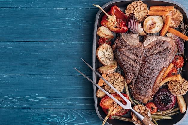 Concepto de una cena maravillosa para dos de un delicioso y jugoso filete de res veteado de granjero a la parrilla con verduras al horno