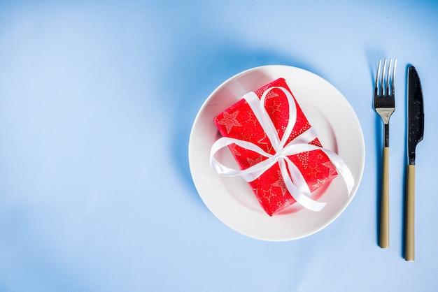 Concepto de cena de navidad con plato y caja de regalo