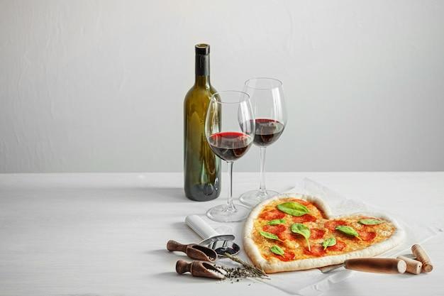 Concepto de cena romántica para dos con vino tinto y pizza en forma de corazón. cena para el dia de san valentin