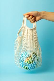 Concepto de cero residuos. bolso de cuerda en una mano femenina con globo terráqueo. bolsas de plástico gratis