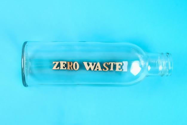 Concepto de cero residuos. botella de vidrio vacía para cero residuos de compras y almacenamiento sobre fondo azul.