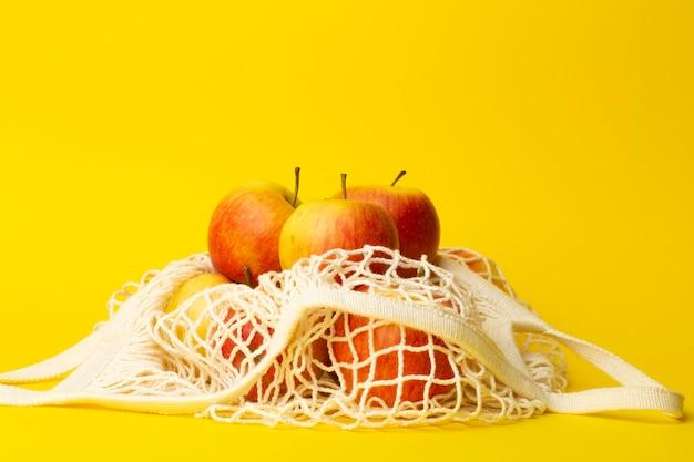Concepto de cero residuos. manzanas en una bolsa de cadena sobre un fondo amarillo. concepto de bolsas de plástico en supermercados y tiendas.