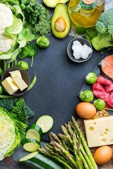 Concepto de ceto de nutrición de dieta equilibrada. surtido de ingredientes alimenticios cetogénicos bajos en carbohidratos saludables para cocinar en la mesa de la cocina. verduras, carne, salmón, queso, huevos. fondo de vista superior