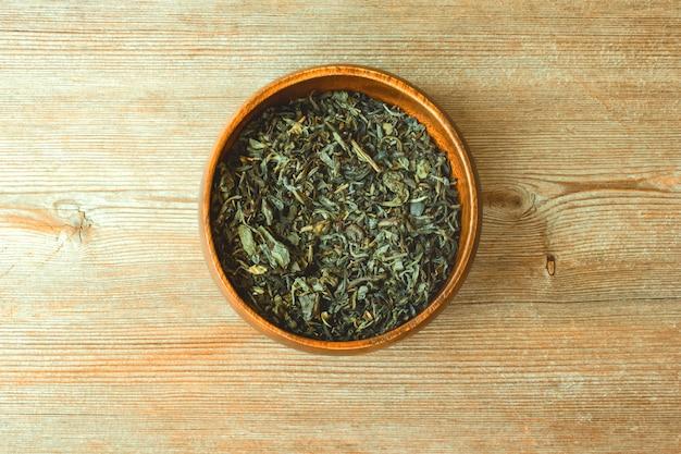 Concepto chino, hojas de té secas verdes japonesas en el cuenco redondo de bambú de cerca en la vista superior de madera natural. espacio de copia de texto